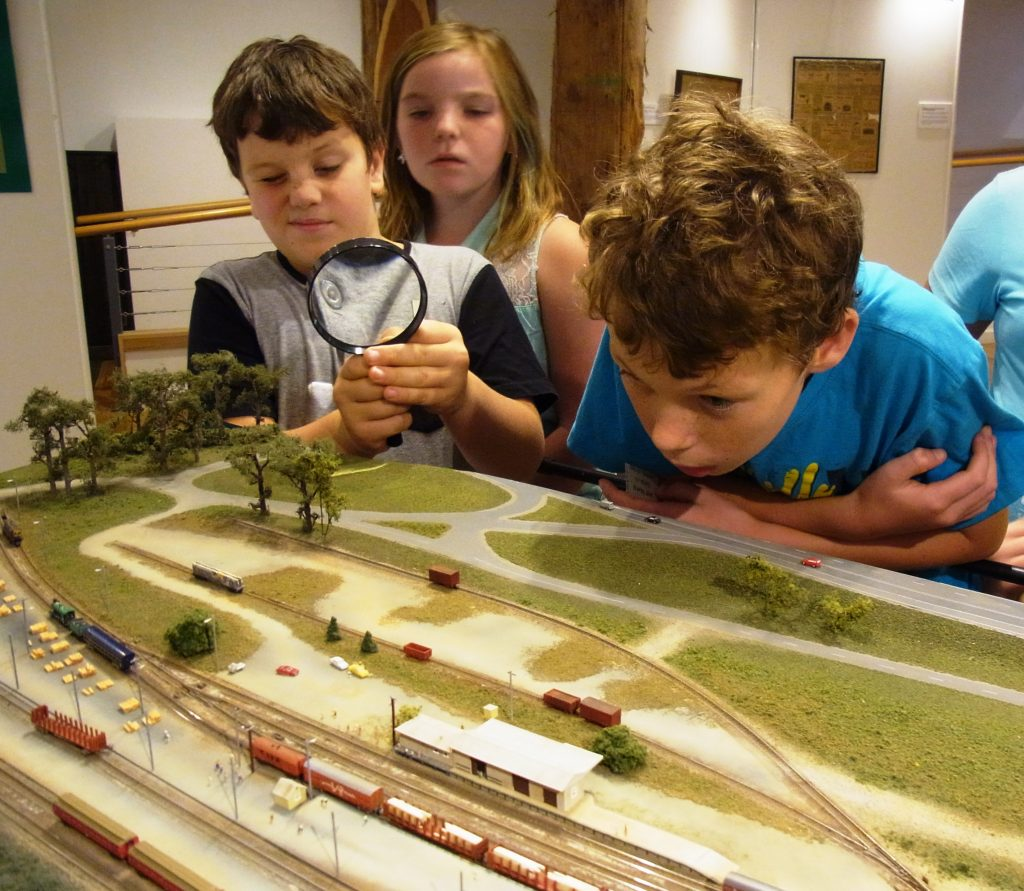 Children at the Orbost Railway 100 Years Exhibition taking a close look at a scale model of the Railway
